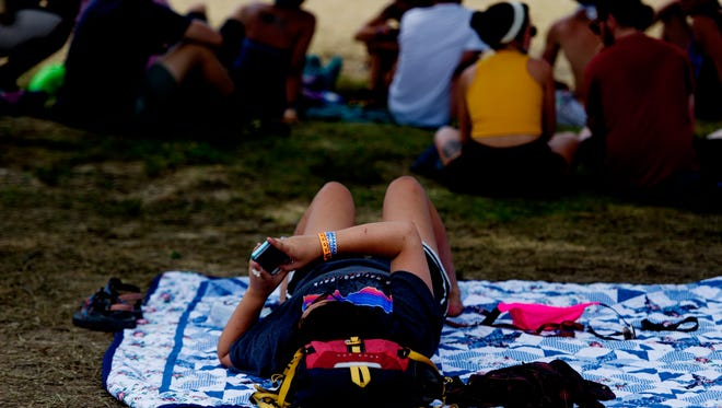 A fest-goer uses their cell phone at Bonnaroo Music and Arts Festival in Manchester, Tennessee on Sunday, June 11, 2017.