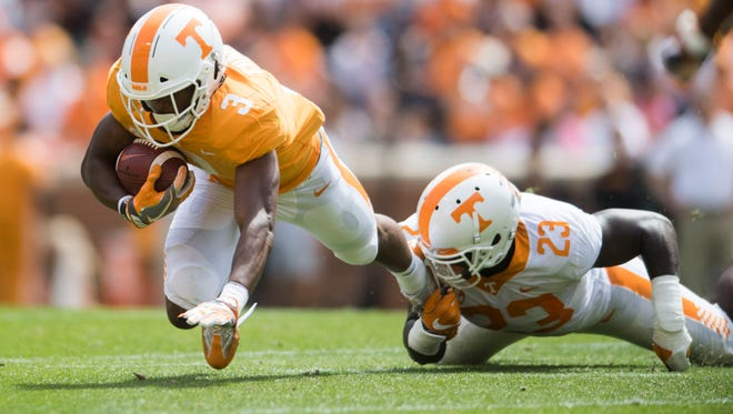 Tennessee running back Ty Chandler (3) is taken down by Tennessee linebacker Will Ignont (23) during the Tennessee Orange & White spring game at Neyland Stadium at University of Tennessee Saturday, April 21, 2018.