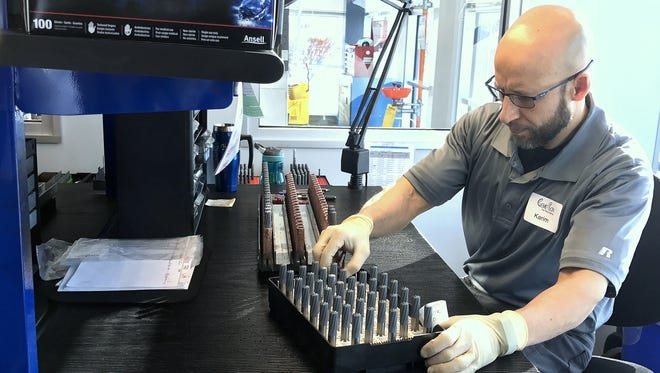 CemeCon Inc. employee Karim Zenati sorts drill bits before they are infused with a diamond coating at the company's Big Flats facility.