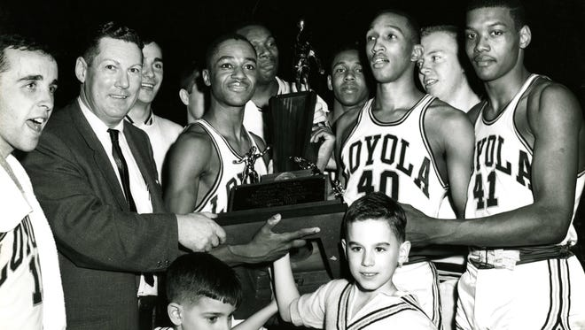 The 1963 Loyola team celebrates its NCAA championship. Racine's Chuck Wood, the team's sixth man, can be seen partially hidden behind coach George Ireland on his left.