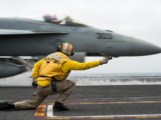 Lt. Justin Otto gives the signal to launch an F/A-18E Super Hornet on the flight deck aboard the aircraft carrier USS John C. Stennis earlier this month.