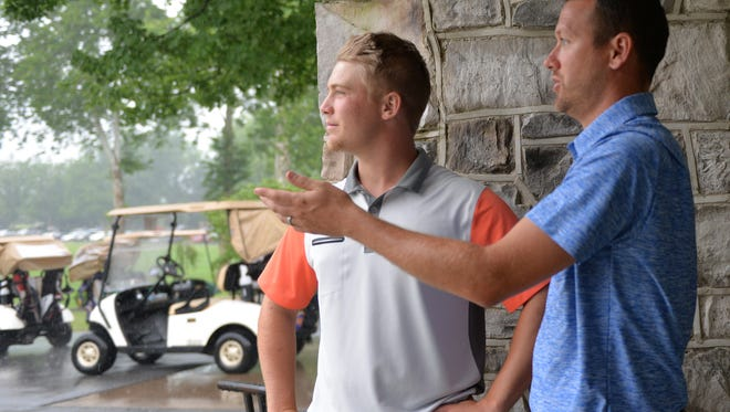 From left, local golfers Noah Firestone and Ryan Weaber wait for the rain storm to pass at the W. B. Sullivan Invitational Fourball held at Lebanon Country Club on Saturday.