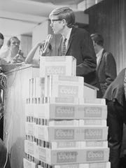 "CSU's student government president Doug Phelps stand behind a pyramid of Coors beers during a ""drink-in"" protest of 1968."