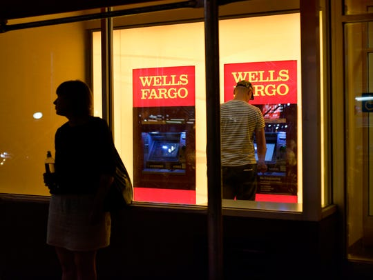 In this Sept. 21, 2016, file photo, a customer uses a Wells Fargo bank ATM in New York.