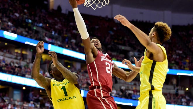 Buddy Hield of Oklahoma lays the ball up Saturday between Jordan Bell and Tyler Dorsey of Oregon.
