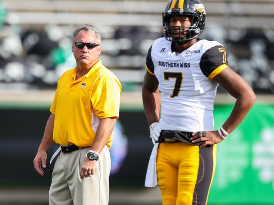Southern Miss Golden Eagles head coach Jay Hopson watches his quarterback Kwadra Griggs (7) warm up before their game against the Marshall Thundering Herd at Joan C. Edwards Stadium.