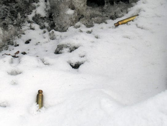 Bullet shell casings lie in the snow near the site