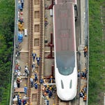 Workers make repairs to a bullet train Monday after it came off the rails in earthquake-hit Kumamoto, Japan.