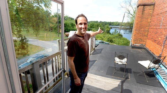 """Milton Theatre executive director Fred Munzert shows what he calls his """"office"""" --  the roof with a view of the Wagamon's Pond dam."""