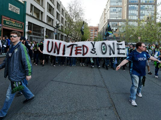 Members of the Emerald City Supporters, a Seattle Sounders supporters group, carry a banner Saturday, April 16, 2016, in Seattle before an MLS soccer match between the Seattle Sounders and the Philadelphia Union. A member of the group said the banner was to show support for a member of the District Ultras, a supporters group for the MLS team D.C. United, who was sanctioned for using a smoke device before a D.C. United match earlier this year. (AP Photo/Ted S. Warren)