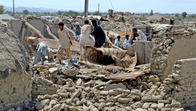 Pakistani villagers look Sept. 25 for belongings in the rubble of their homes destroyed in an earthquake in Baluchistan province, Pakistan.