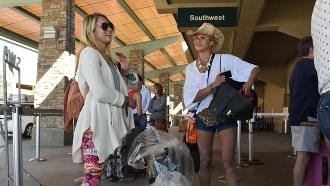 Covered with playa dust, Brielle Gearson, left, and Dina Nadezhdina wait to check in for their flight home to Los Angeles on Monday morning. Their baggage is wrapped in mandatory plastic because the playa dust can clog the conveyor system.