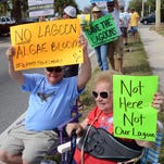 Mike and Fran Krane of Baytree hold signs seeking support from drivers during a rally for the Indian River Lagoon in Cocoa Beach.