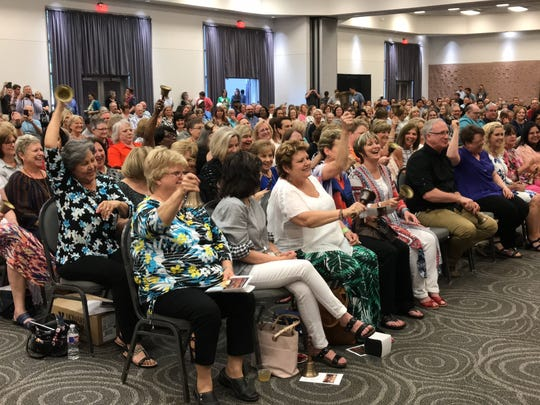 Retiring Abilene Independent School District teachers hold their bells high and ring them loud during a ceremony Thursday.