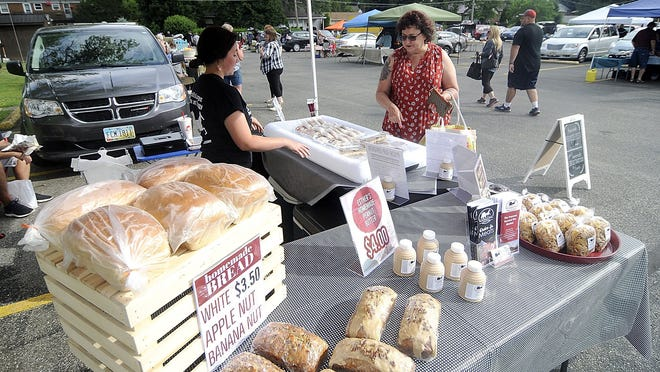 Maddie Shonkwiler helps customer Cheryl Smith with her purchase at the Beyond Measure Market's tent at the farmers' market at Christ United Methodist Church on Saturday. Saturday was the first farmers' market of the season at Christ United Methodist Church.