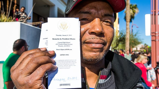 Dowayne Elam, 53, of Glendale, stands across the street from Central High School in Phoenix to show off his ticket to see President Obama speak on Thursday, Jan. 8, 2015.