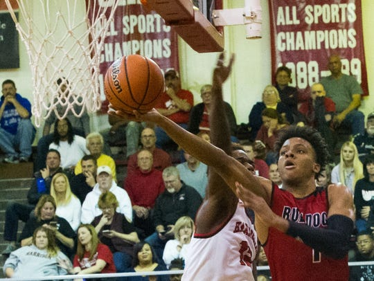 Harrison's Ja'Korion Lindsey (12) tries to block New Albany's Romeo Langford (1) as he goes up for a shot in the second quarter at Harrison High School, Dec. 3, 2016.