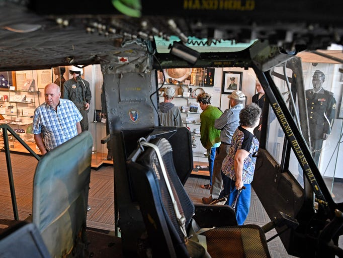 Looking through a Vietnam era helicopter, visitors