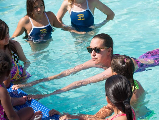 An instructor demonstrates swimming and pool safety