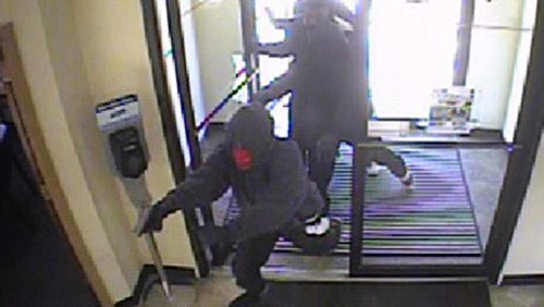 Robbery suspects are shown, Monday, Aug. 4, 2014, in surveillance footage as they enter the Industrial Federal Credit Union on Meijer Drive in Lafayette at about 9:25 a.m.