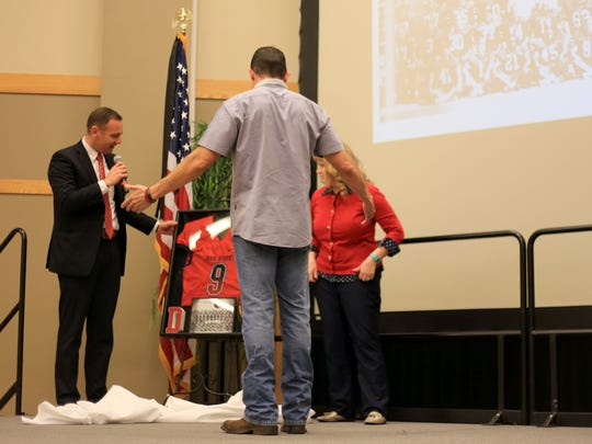 "Dixie State University officials present former CIA security contractor Kris ""Tanto"" Paronto with a framed version of the jersey he wore when he was a football player at Dixie State in the early 1990s."