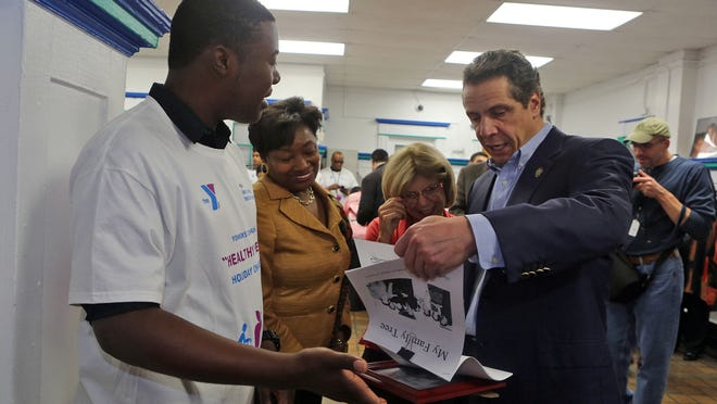 Dennis Richmond Jr., left, presents Gov. Andrew Cuomo last year with genealogical material he'd collected online. Looking on are state Sen. Andrea Stewart-Cousins and state Assemblywoman Shelley Mayer.