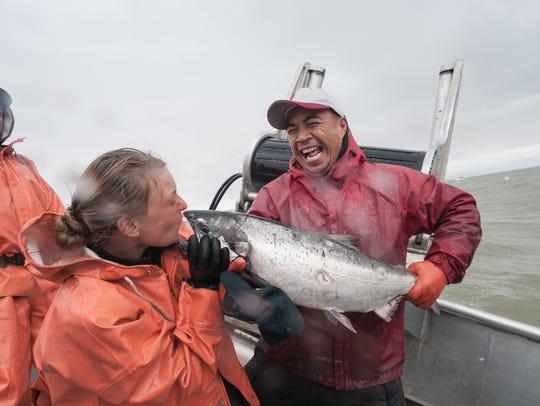 Sockeye salmon is kissed by crewmember.  Naknek River,