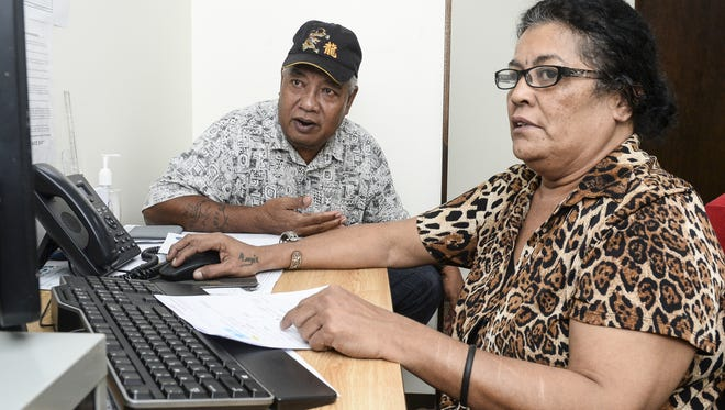 In this Dec. 2, 2016, file phtoo, Angeles Mariur, right, assists Yigo resident Swainer Airam, 62, in searching for a job at the Guam Department of Labor's American Job Center