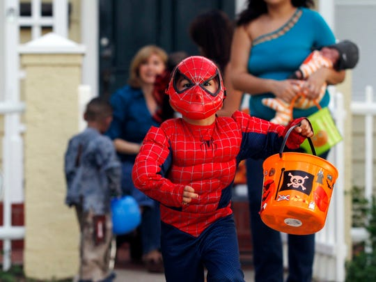 A trick-or-treater runs down the sidewalk after collecting candy Thursday, Oct. 31, 2013 along Del Mar Boulevard in Corpus Christi