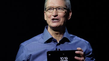 Apple CEO Tim Cook holds up the new iPad Pro at a media event in San Francisco on Sept. 9, 2015. Eli Lilly already has 15,000 iPads and is upgrading to the iPad Pro.