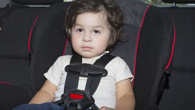 Esdres Lopez-Gascar, 2, sits in his new car seat he got during a car seat safety class called Children are Priceless Passengers at Banner Desert Medical Center in Mesa on June 20, 2015.