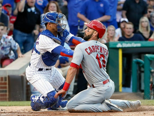 Chicago Cubs' Willson Contreras, left, tags out St. Louis Cardinals' Matt Carpenter, right, during the first inning of a baseball game, Sunday, July 23, 2017, in Chicago. (AP Photo/Kamil Krzaczynski)