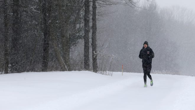 A woman jogs on a trail at the South Chagrin Reservation, Tuesday, Jan. 19, 2016, in Solon, Ohio,