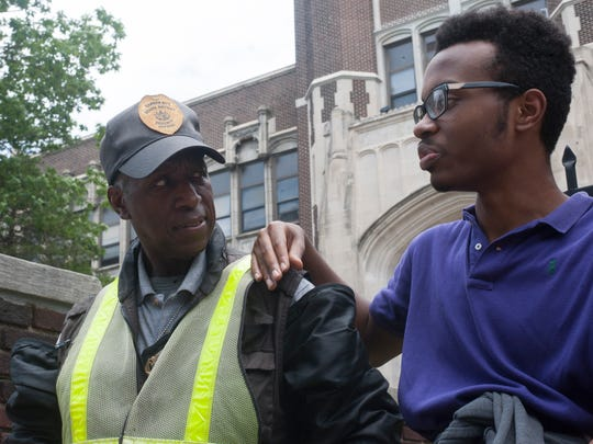 Camden High Student Devine Bowens talks to security guard Terry Pace outside the school, known as the Castle on the Hill.
