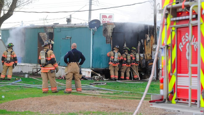 Firefighters at the scene of a mobile home fire at 4506 W. 12th St. on Tuesday, May 20, 2014.