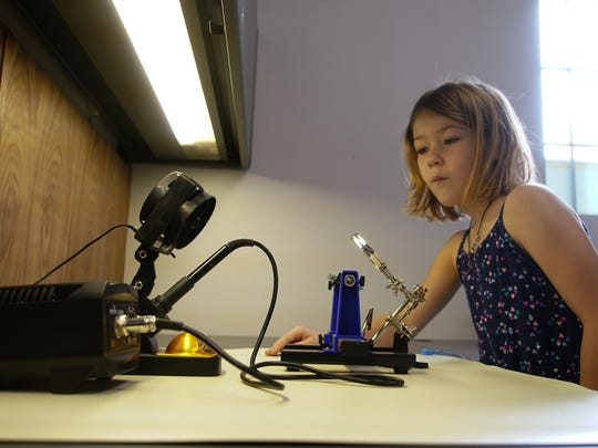 Daphne Hankins, 7, checks out a laser at NextFab, a