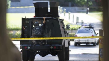 A SWAT team member watches as a man barricades himself in his car while blocking an intersection on the north side of the state Capitol Monday, April 18, 2016 in Sacramento, Calif.