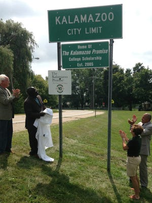 Kalamazoo Promise Executive Director Bob Jorth, from left, Kalamazoo Mayor Bobby Hopewell, former Kalamazoo Promise Executive Director Janice Brown and Kalamazoo Promise Executive Director of Community Relations Von Washington Jr. applaud Friday, Aug. 14, 2015, in Kalamazoo, Mich., following the unveiling of city limit signs honoring the Kalamazoo Promise and its 10-year anniversary. Announced in 2005, the anonymously funded program that pays the college tuition of students from the Kalamazoo public school district has given out $67 million in scholarships, and students have earned more than 850 degrees and post-secondary credentials. Close to 4,000 students have taken advantage.