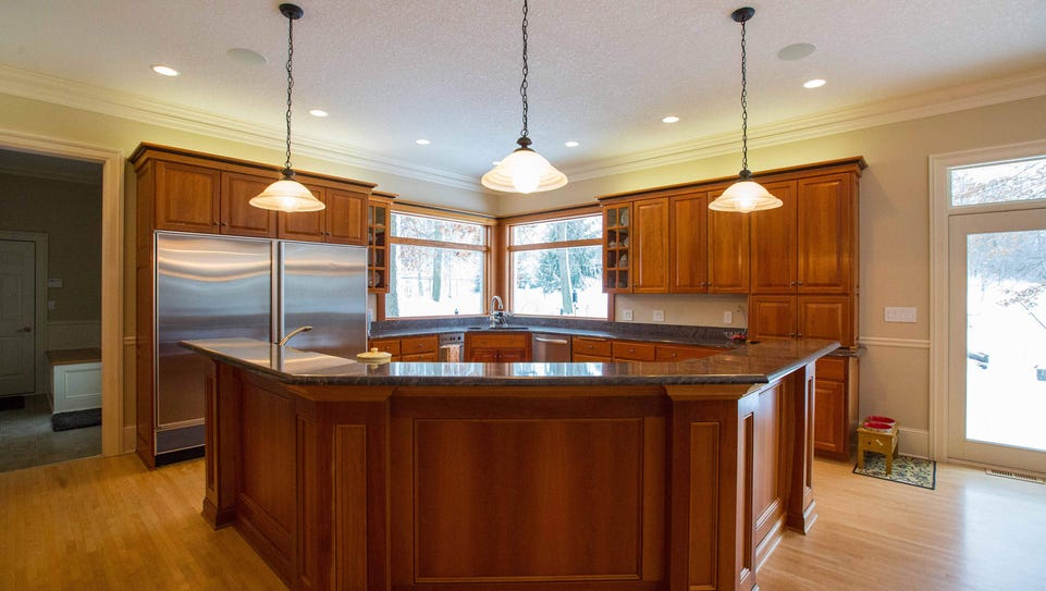 Open cherry kitchen with large island. All brick ranch