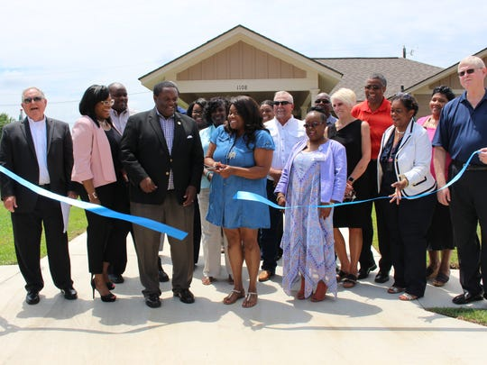 Monroe Housing Authority and City of Monroe representatives unveil the first of 50 new homes in Robinson Place with new resident Disha Ward.