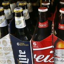 Bottles of Budweiser and Miller Lite beer. Budweiser's parent company is buying Miller's parent company.
