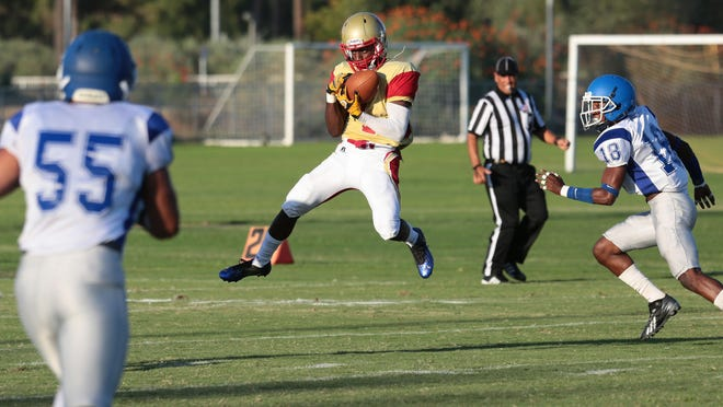 College of the Desert's Reginald Macon completes a pass against Santa Monica on Saturday in Palm Desert.