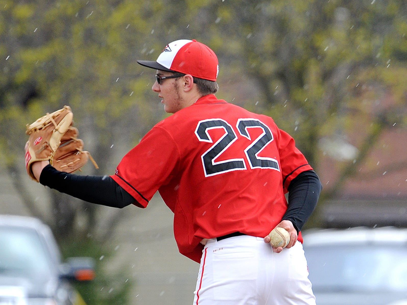 Bucyrus' Gavin Lewis prepares to throw another pitch during their game against Upper Sandusky as a snow/hail mixture falls from the sky Wednesday evening.