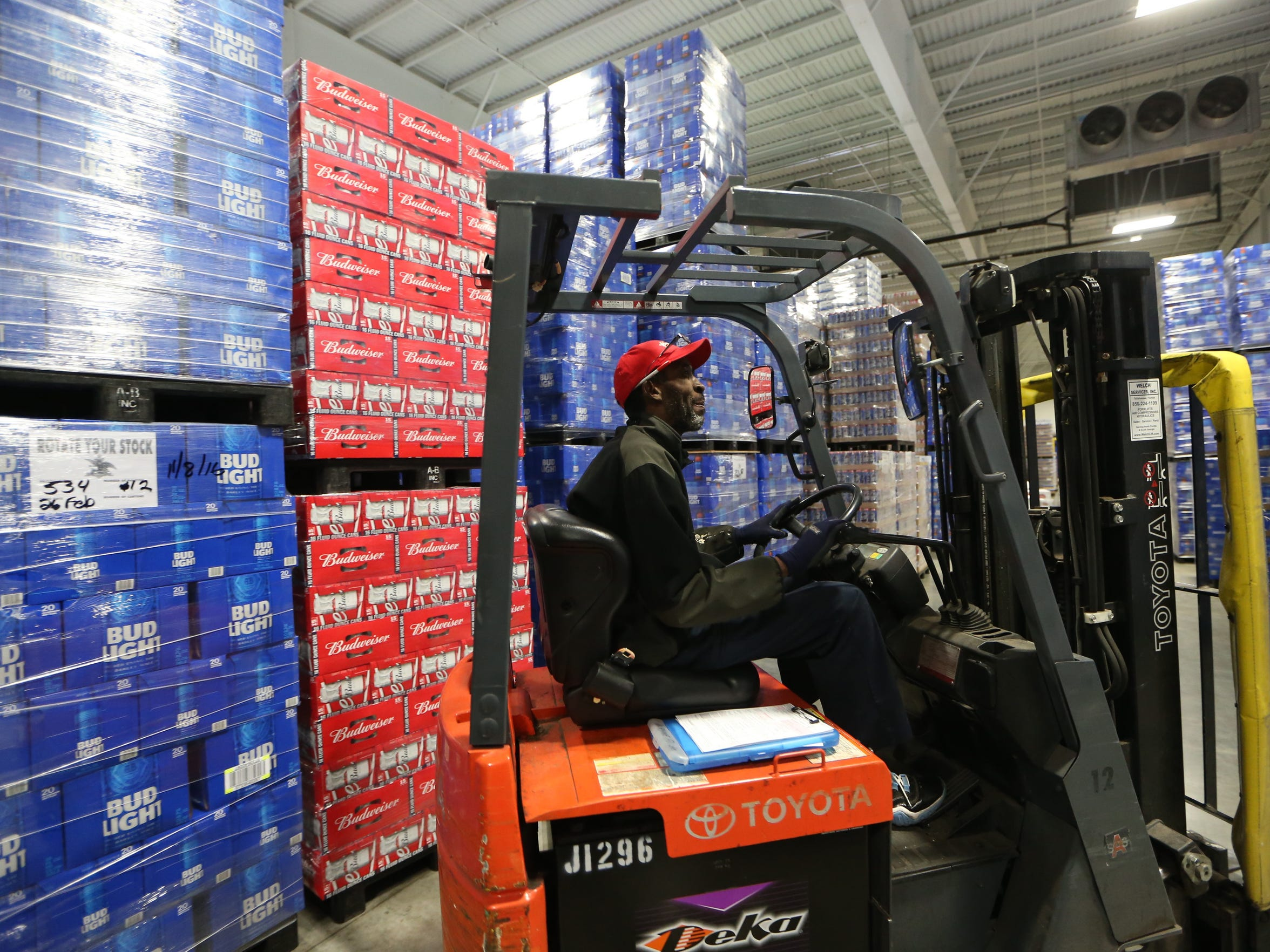 Workers move large palates of traditional Anheuser Busch
