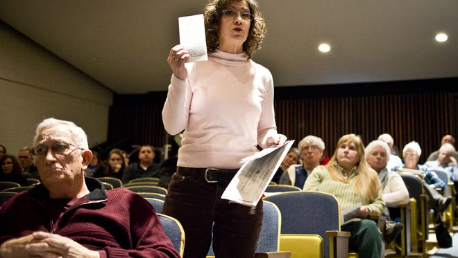 Carrie Neuschel, who questions the benefits of a 1 percent Colchester local option tax, holds up literature by the Colchester Community Development Corp. in support of the tax during the town's 2015 annual meeting.