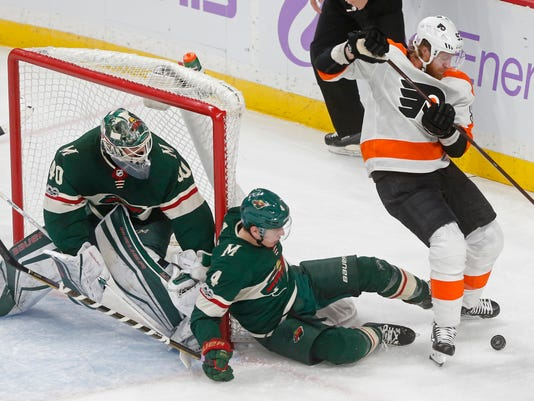 Minnesota Wild goalie Devan Dubnyk, left, watches as Mike Reilly falls while defending against Jakub Voracek, right, of Czech Republic, during the first period of an NHL hockey game Tuesday, Nov. 14, 2017, in St. Paul, Minn. (AP Photo/Jim Mone)