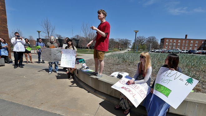 Drake freshman John Noble, center in red shirt, 19 of Grand Island, Neb., speaks to other students and members of the Des Moines community during a protest at the Iowa Energy Forum featuring former National Security Adviser General James Jones, who spoke about the Keystone XL Pipeline and other topics.   Noble was one of the organizers of the protest. The forum was held at the Olmsted Center on the Drake University campus on Tuesday afternoon April 22, 2014.