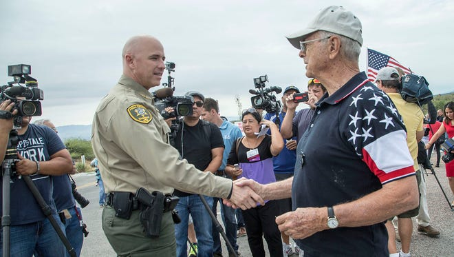 Pinal County Sheriff Paul Babeu, on left, shakes hands with the opposing group leader Robert Skiba while they awaited for a busload of immigrant children heading to a detention facility near Mt. Lemmon highway on Tuesday July 15, 2014.