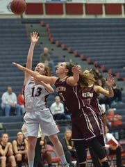 Shippensburg Raiders Colleen Young (13) takes a shot at the basket while being pressured by Kelsey Watson (15) of Kutztown University during a girls basketball game in Shippensburrg, Pa on Saturday, Dec. 19, 2015. Young scored during the second quarter 25-9.