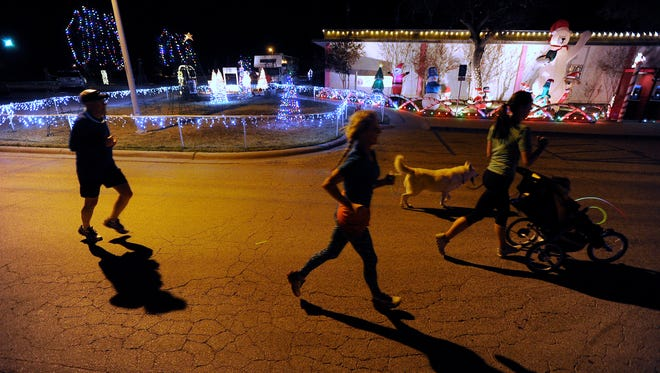 Runners pass by one of the displays during the Christmas Lane 5K on Thursday, Dec. 1, 2016, at the Abilene State Supported Living Center.